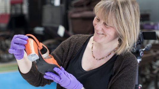 Helen Johnson with shoe from museum collection